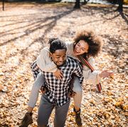 cheerful african american couple piggybacking in autumn at the park