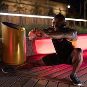 cheerful ethnic athlete warming up at night