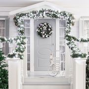 house entrance decorated for holidays christmas decoration garland of fir tree branches and lights on the railing