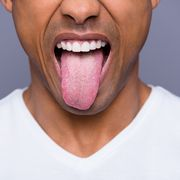 close up cropped portrait of his he handsome attractive well groomed virile funky guy wearing white shirt showing tongue out isolated over gray violet purple pastel background
