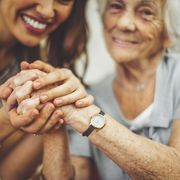 close up of a smiling nurse holding a senior woman's hand