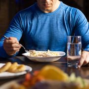 close up of athlete eating pasta dish
