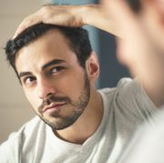 closeup of handsome man looking in mirror at home