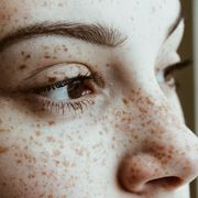 close up of thoughtful woman with freckles on face