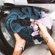 wet laundry going into clothes dryer