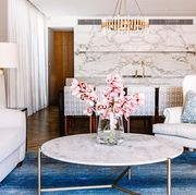 great room with blue carpet and marble kitchen backsplash