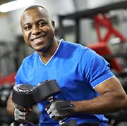 content black male holding weights in gym