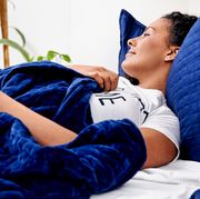 woman lying in bed with blue gravity blanket and pillows