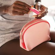 woman with lip gloss and cosmetic bag