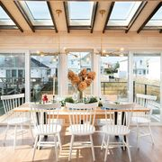 dining room in cottage surrounded by windows overlooking water
