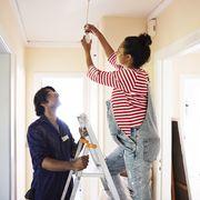 couple changing light bulb while renovating home