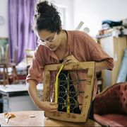Craftswoman Measuring Old Chair Seat For Reupholstery