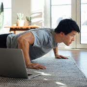 cropped shot of young man doing pushup in front of laptop at home