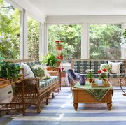 screened in porch, blue and white striped rug, wicker chairs and sofa with green and white cushions, indoor plants