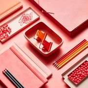 pink and red office supplies in desk organizers
