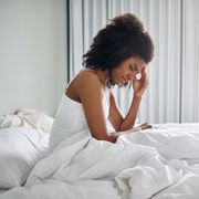 woman sitting in bed in pain