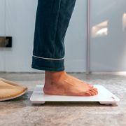 man standing in pajamas on digital scale