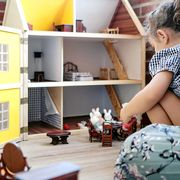 young kid playing with doll house