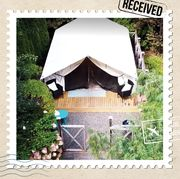 this glamping tent is tucked into an award winning, acres long garden