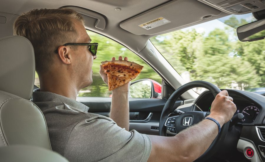 You Wouldn't Eat Pizza While Driving. So Why Are People Talking to It?