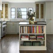 green cabinets kitchen, black countertops, books