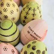 pink, yellow, and green wooden eggs and blue speckled ones