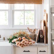 orange flowers by kitchen sink