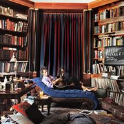 rolling stones keith richards holding a guitar on a chaise longue in a massive library room