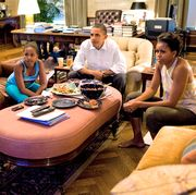 president barack obama, first lady michelle obama, and their daughters malia and sasha sit watching television