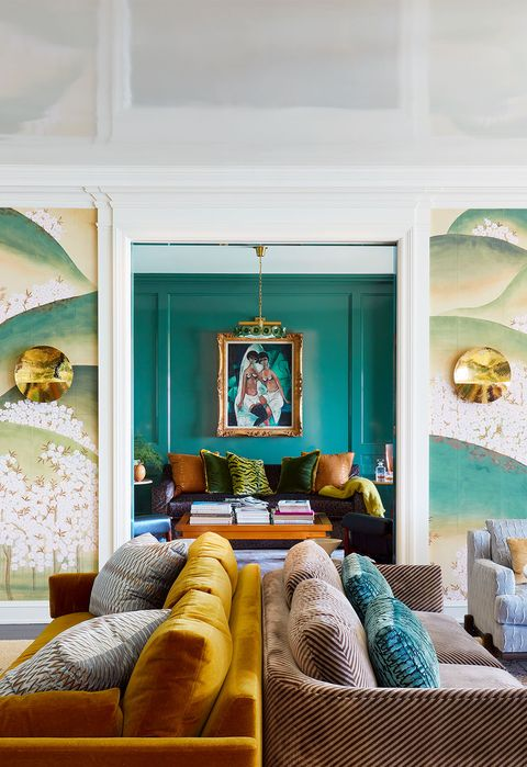 living room with back to back sofas and a large painted wall behind it