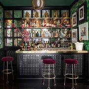 home bar with gold counter and red velvet seats