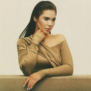 mckayla maroney posing on a balance beam in a beige gown