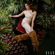 leslie grace posing in tan jumpsuit and fuzzy brown boots