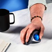 ergonomic mouse on desk with mug and laptop