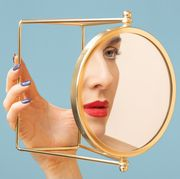 woman looking at face in gold mirror