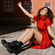 woman in red turtleneck dress and black boots sitting on ground