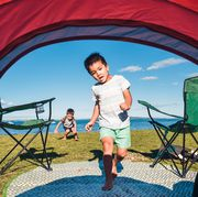 boy running into camping tent