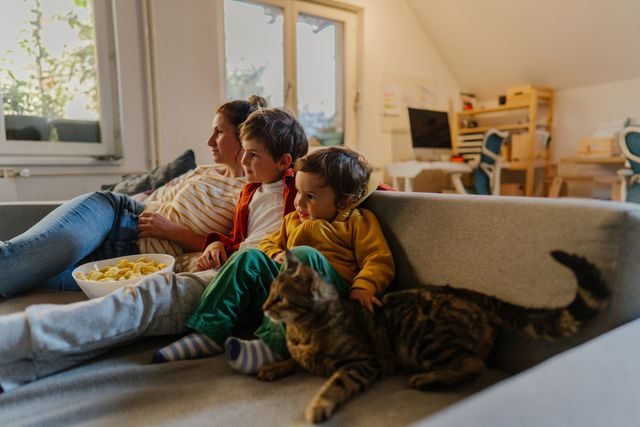 family watching television on the couch with pet cat while eating snacks