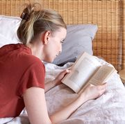 woman wearing a red shirt and jeans lying on bed reading a feel good book in sunlight