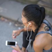 Female athlete listening to music with smartphone