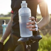 female cyclist holding water bottle
