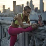 Female stretching hamstrings before run