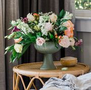 flowers in vase next to bed