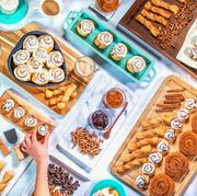 marble table full of cinnabon cinnamon rolls and desserts three hands reaching for treats