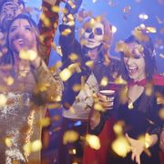 Friends in Halloween costumes dancing among confetti