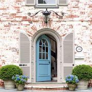 light blue front door with brick home