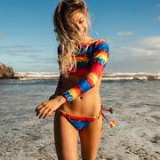 Smiling Young Woman Wearing Bikini While Walking Against Sea At Beach