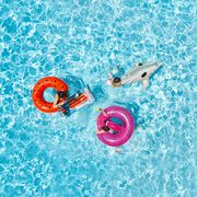 Three childred on inflatable floats in swimming pool