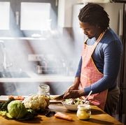 young black man chopping vegetables while preparing food in the kitchen copy space