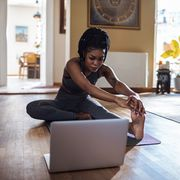 close up of a young woman learning yoga online from her laptop